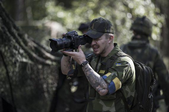 Här dokumenterar Croona ett par soldater som maskerar en lastbil. Maskering hör till kategorin fältarbete för överlevnad.