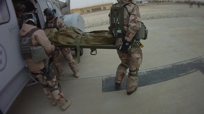 Läkaren, sjuksystern, färdmekanikern och uppdragsspecialisten lyfter ut patienten för att lämna över honom till den afghanska ambulansen. Foto: Younggun