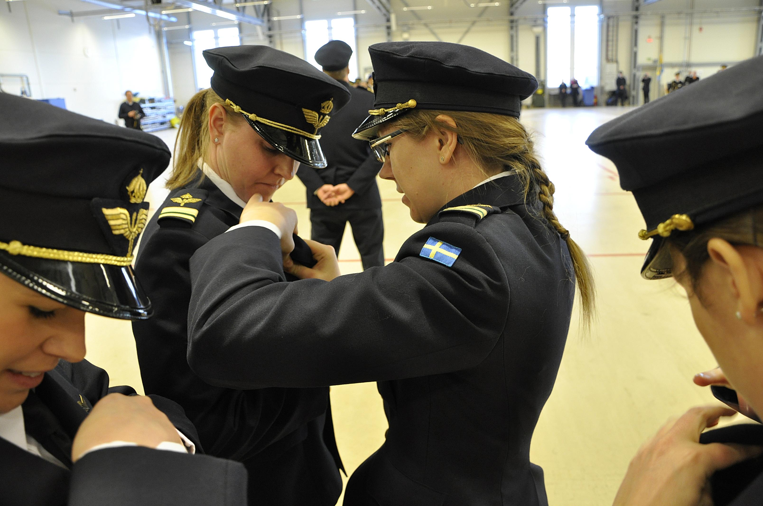 Meteorologen lt Charlotte Boström hjälper sin kamrat att anbringa meteorologmärket på uniformen.