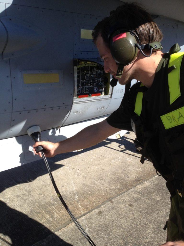 Hjälpmekaniker klargör flygplan