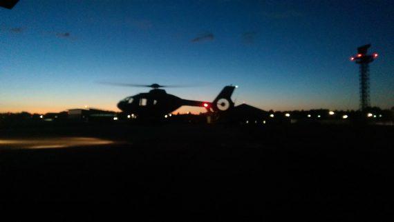 """Helikoptern har precis lyft från """"plattan"""" och är på väg ut för ett pass medan det sista solljuset försvinner."""