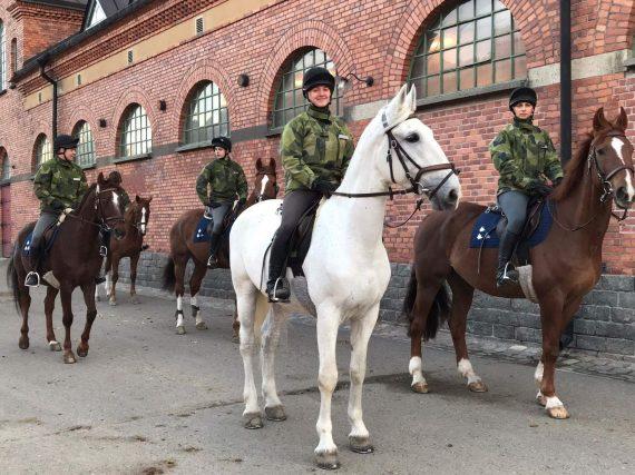 Foto: Lena Berg som hjälper till att rida hästarna genom Blå stjärnan. Här ska vi rida ut och jag har en av mina favorithästar Ymer(den vita).