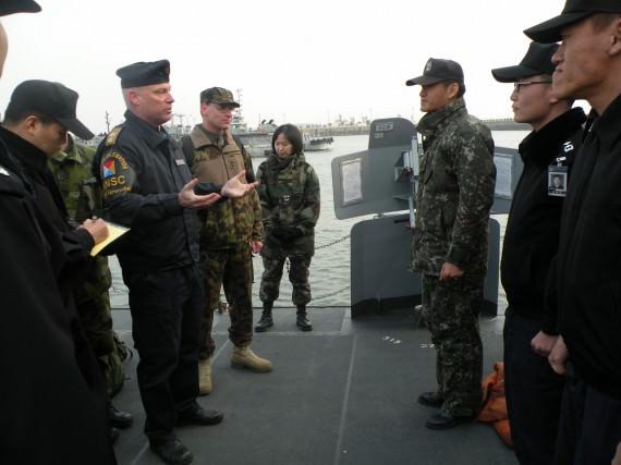 Konteramiral Grenstad förklarar för fartygschefen vad NNSC gör ombord