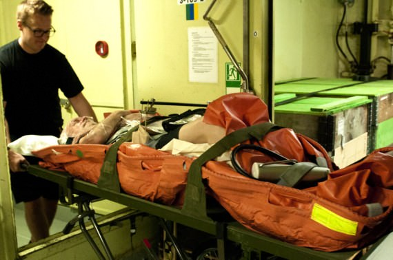 Det behövs hjälp av övriga besättningen för att förflytta båren med patienten genom fartyget. Foto Anders Kallin/Försvarsmakten