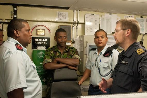 Carlskronas förstemaskinist Christoffer Lineskär berättar om arbetet i maskincentralen för representanter från den seychelliska kustbevakningen. Foto Anders Kallin/Försvarsmakten