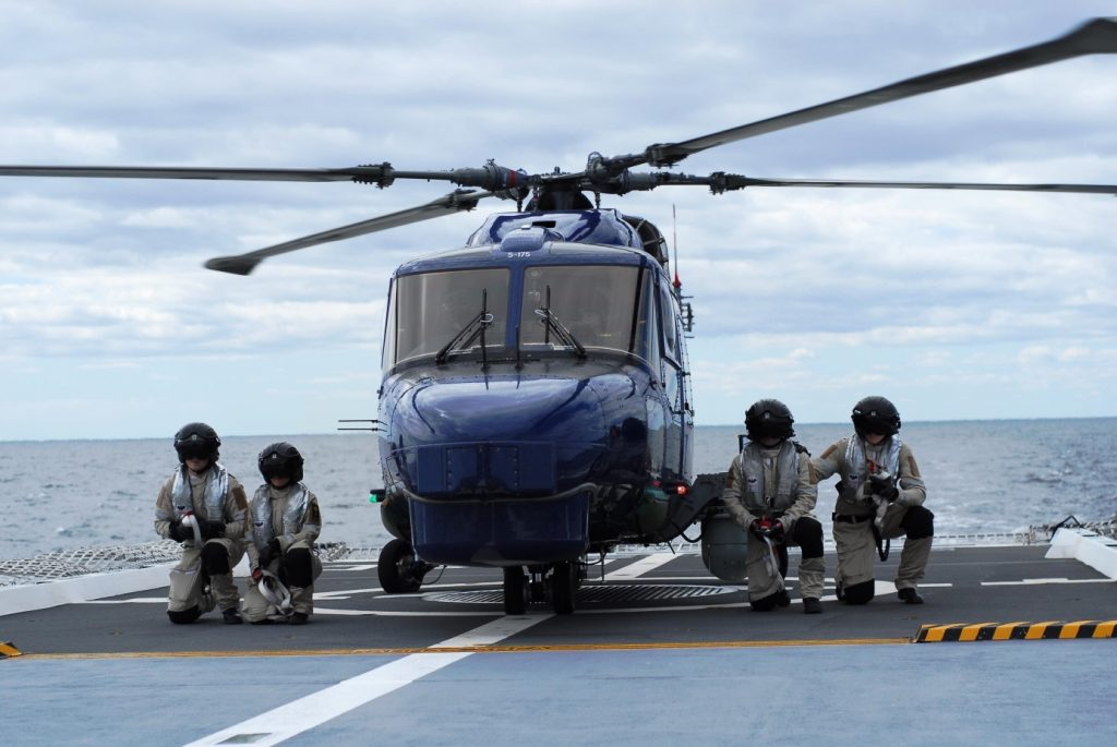 Personalen på helikopterdäck har avlägsnat surrningarna; de ställer upp för att tydliggöra att samtliga fyra surrningar är borttagna varpå helikoptern snart är redo för start.