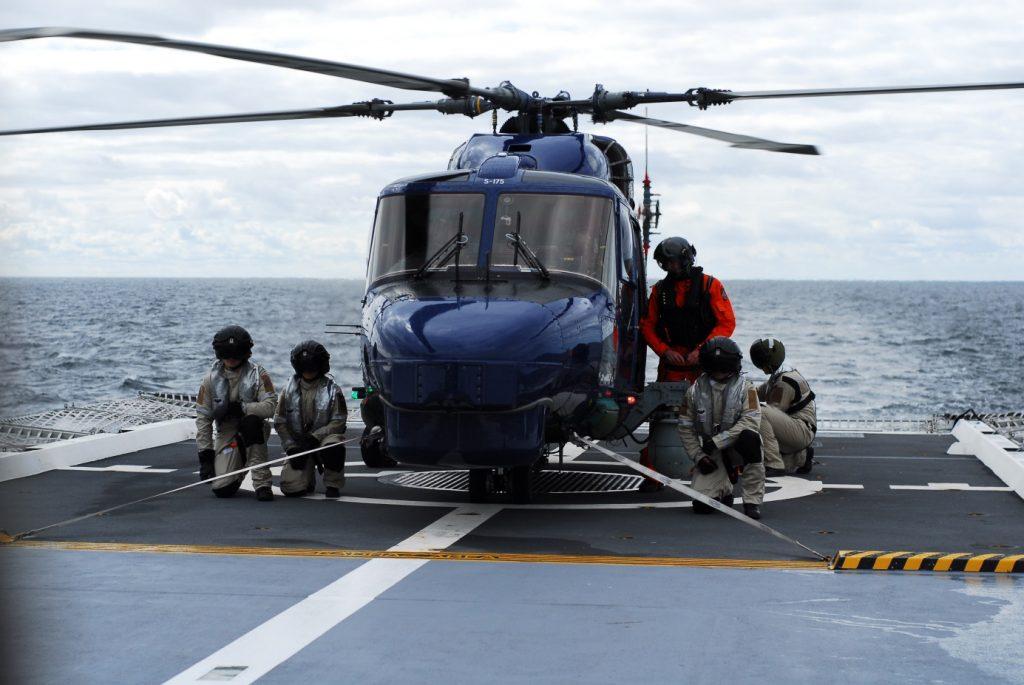 Den danska lynxhelikoptern surrad till däck med spännband. Under helikoptern syns gallret i vilket harpunen fäster. I orange dräkt syns den danska färdmekanikern.