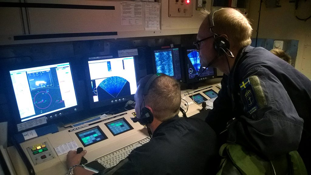 Vaktchefen och UsO (Undervattenstrids Officer) manövrerar fartygets ROV (Remotely Operated Vehicle) med sprängladdning fram till minan inför sprängning.